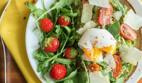 Une tartine avocat, oeuf mollet et sa salade roquette fraises.